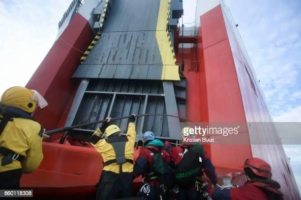 Greenpeace activists board the cargo ship Elbe Highway September 21st 2017 Thames Estuary Kent United Kingdom Greenpeace volunteers in kayaks speed...