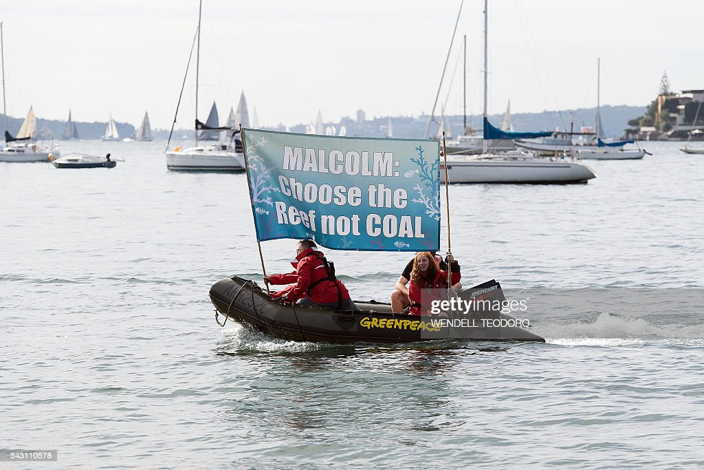 Greenpeace activists carry a banner on a boat in front of Australian Prime Minister Malcolm Turnbull's residence in Sydney on June 26, 2016. Hundreds of activists gathered in Sydney demanding more action on climate change from the Coalition. / AFP / WENDELL