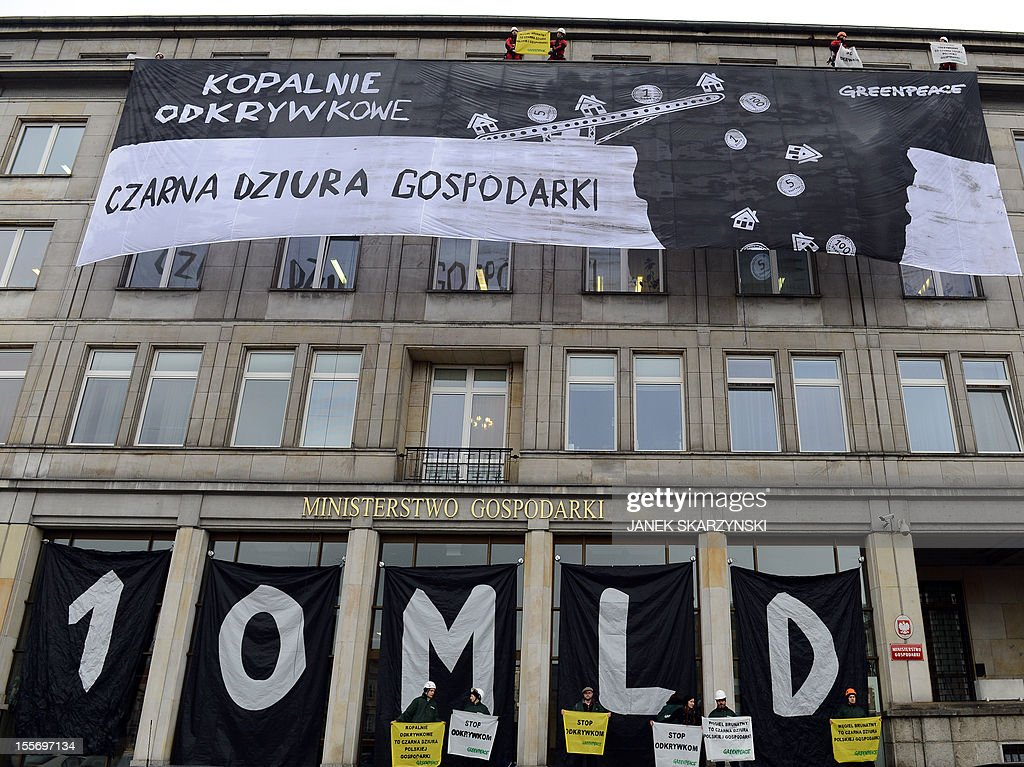 Greenpeace activists drape Poland's Economy Ministry in Warsaw with protest banners against the development of new open pit coal mines in Poland which they argue will claim a high environmental and financial toll on November 7, 2012. The banner reads 'open pit coal mines- black whole of the economy'. AFP PHOTO/JANEK SKARZYNSKI