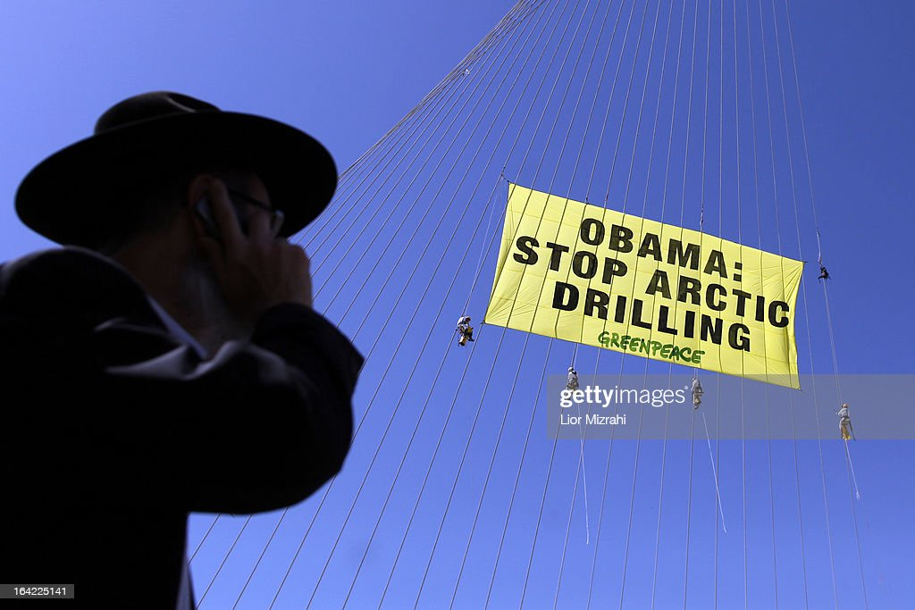Greenpeace activists hang a banner saying 'Obama Stop Arctic drilling' on the cables of Jerusalem's Chords Bridge on March 21, 2013 in Jerusalem, Israel. This is President Obama's first visit as president to the region, and his itinerary includes meetings with the Palestinian and Israeli leaders as well as a visit to the Church of the Nativity in Bethlehem.