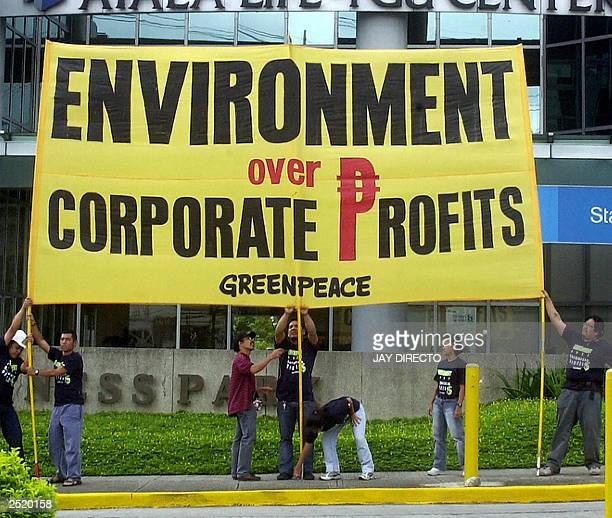 Greenpeace activists hang a giant protest banner at a building in Alabang town suburban Manila 12 September 2003 where US agrichemical company firm...