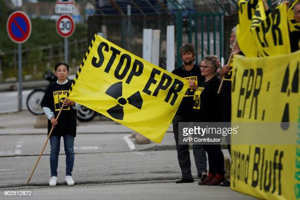 Greenpeace activists hold a banner as they stand in front of the European Pressurised Reactor project nuclear plant of Flamanville northwestern...