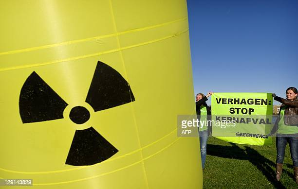 Greenpeace activists hold an antinuclear sign and banner on October 13 in Amsterdam The banner reads 'Verhagen stop nuclear waste' A Greenpeace...