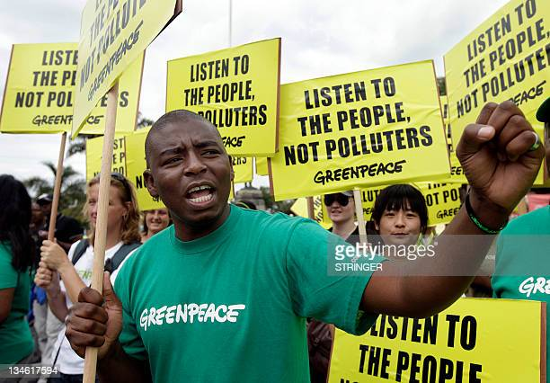 Greenpeace activists hold banners and shout slogans during a protest to demand action to combat global warming as experts hold UN climate talks on...