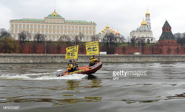 Greenpeace activists hold flags reading 'Free the Arctic 30' as they go past the Kremlin by boat to protest the detention of the 'Arctic 30' a group...