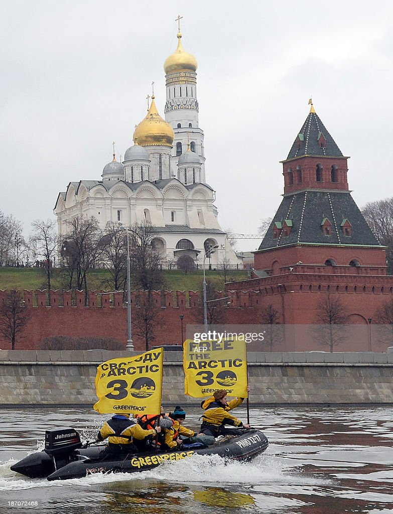 Greenpeace activists hold flags reading 'Free the Arctic 30' as they go past the Kremlin by boat to protest the detention of the 'Arctic 30', a group of Greenpeace activists, on November 6, 2013, in Moscow. The 'Arctic 30' Greenpeace activists are in prison waiting trial on charges of hooliganism after having taken part in a protest action and attempted to climb a Gazprom oil rig in the Arctic sea. The activist's ship, the Arctic Sunrise, was also seized by Russian security forces.