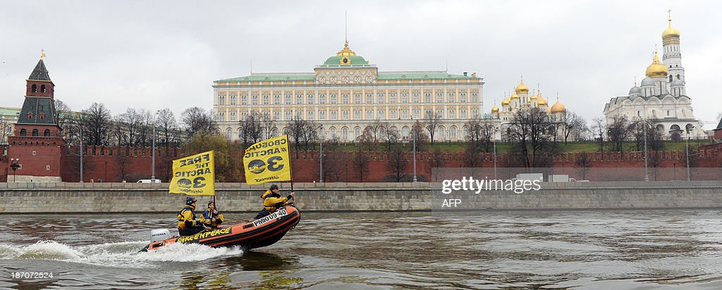 Greenpeace activists hold flags reading 'Free the Arctic 30' as they go past the Kremlin by boat to protest the detention of the 'Arctic 30', a group of Greenpeace activists, on November 6, 2013, in Moscow. The 'Arctic 30' Greenpeace activists are in prison waiting trial on charges of hooliganism after having taken part in a protest action and attempted to climb a Gazprom oil rig in the Arctic sea. The activist's ship, the Arctic Sunrise, was also seized by Russian security forces. AFP PHOTO / VASILY MAXIMOV