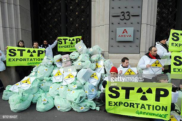 Greenpeace activists hold placards after dumping fake bags of nuclear wastes in front of French nuclear giant Areva's headquarters on February 20...