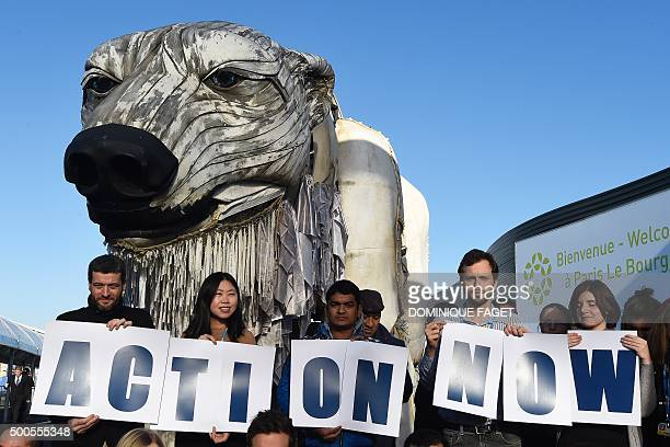 Greenpeace activists hold signs reading 'Action Now' in front of Greenpeace's giant puppet polar bear Aurora during a protest at the COP21 United...