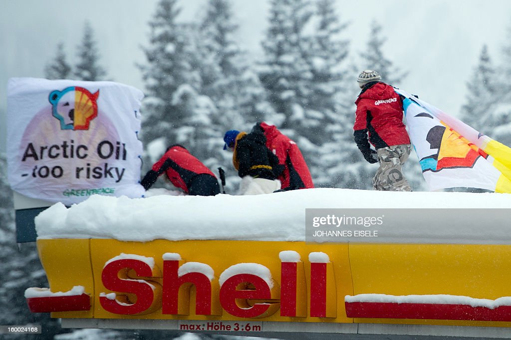 Greenpeace activists install banner on the roof of a filling station during a protest against global oil giant Shell on January 25, 2013 in Wolfgang near the Swiss resort of Davos where the 2013 World Economic Forum (WEF) is taking place. AFP PHOTO / JOHANNES EISELE