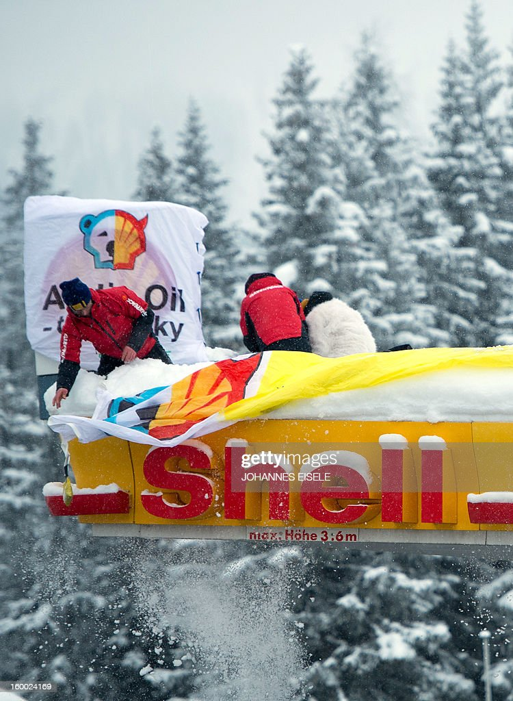 Greenpeace activists install banners on the roof of a filling station during a protest against global oil giant Shell on January 25, 2013 in Wolfgang near the Swiss resort of Davos where the 2013 World Economic Forum (WEF) is taking place.