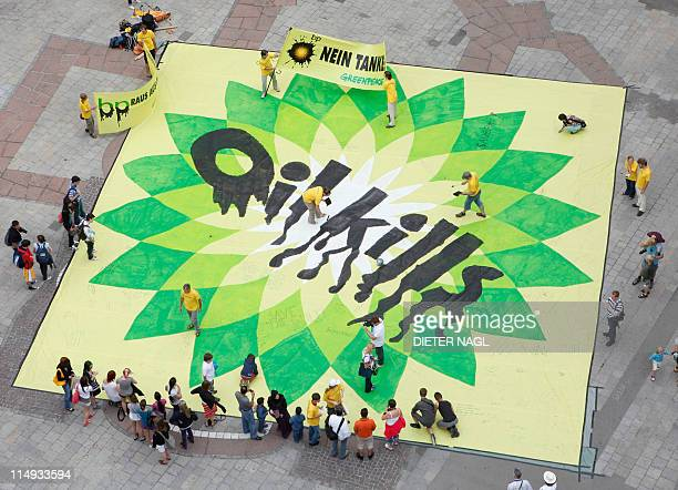 Greenpeace activists invite pedestrians to write a message to the BP oil company on a giant banner reading 'Oil Kills' in the center of Vienna on...