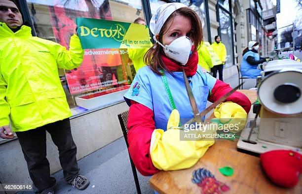 Greenpeace activists make a performance during which they pretend they are sewing contaminated clothes with chemicals represented by little monsters...