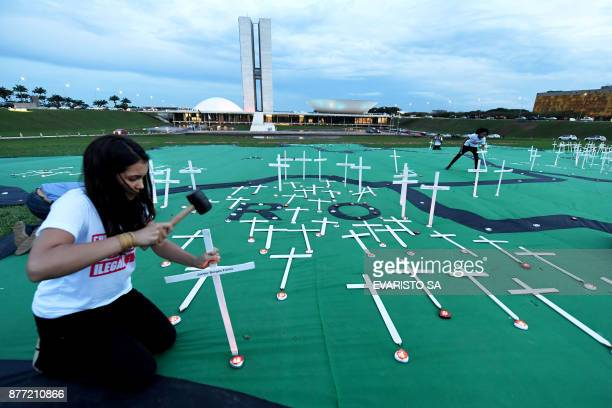 Greenpeace activists place crosses on a huge map to protest against deaths caused by illegal logging in the Brazilian Rain Forest in front of the...