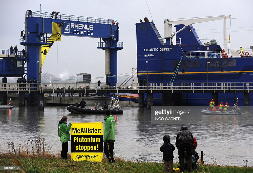 Greenpeace activists protest with a banner reading 'Plutonium Stop!' in front of the Atlantic Osprey' cargo vessel transporting highly toxic MOX fuel from the UK for the nuclear power plant Grohnde on November 18, 2012 in Nordenham, eastern Germany. AFP PHOTO/ Ingo Wagner/GERMANY OUT