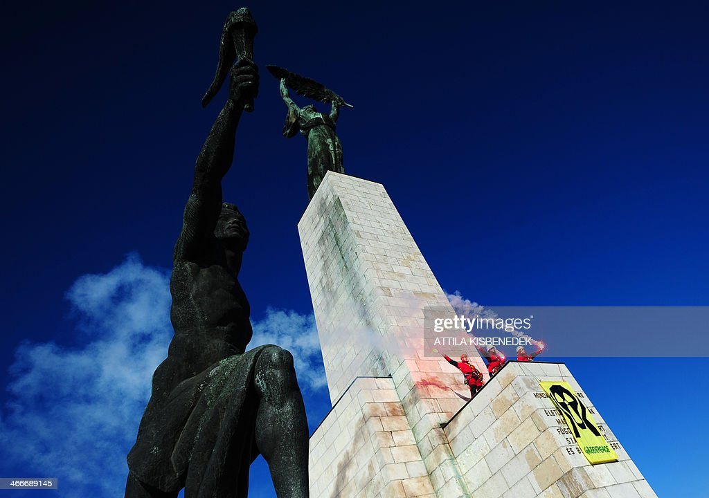 Greenpeace activists protest with their anti-nuclear banner on the monument of Freedom Statue at the Gellert Hill of Budapest on February 3, 2014 during their demonstration against Hungarian government's energy policy and a plan to expand the country's nuclear power plant of Paks. The demonstrators aimed to call attention to the planned process of lifetime extension and expansion of the Hungarian Nuclear Power Plant in Paks, claiming to stop this plans. Representatives of the Hungarian Parliament discuss the expansion plan of Paks power plant today and tomorrow. The text reads 'The memory of all those who sacrified their lives for independence, for freedom and prosperity of Hungary.' AFP PHOTO / ATTILA KISBENEDEK