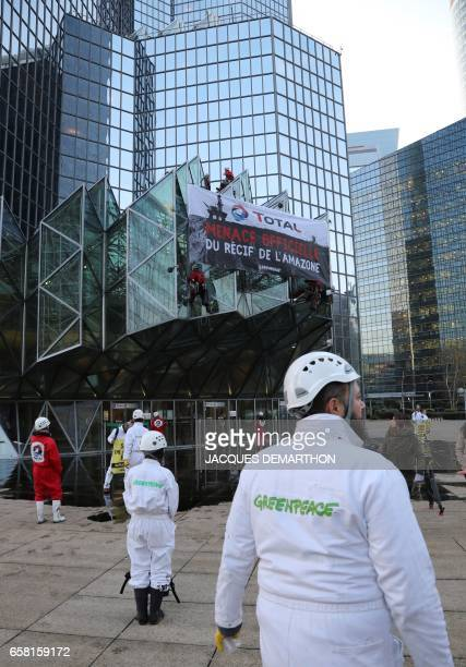 Greenpeace activists stand after pouring molasse in front of French oil giant Total headquarters on March 27 2017 in La Defense district western...