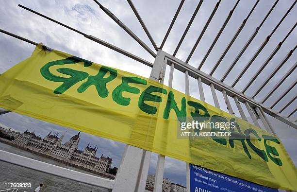A Greenpeace flag hangs on the gates of the parliament as activists prepare for protest on the Danube river in the center of Budapest on June 29 2011...