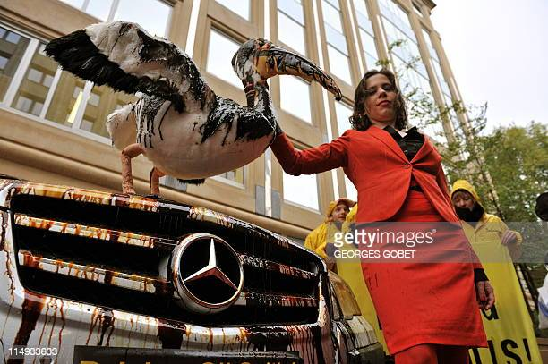 Greenpeace hostesses splatter luxury vehicles with oil on October 20 2010 in front of the Brussels office of the European Carmaker Association to...