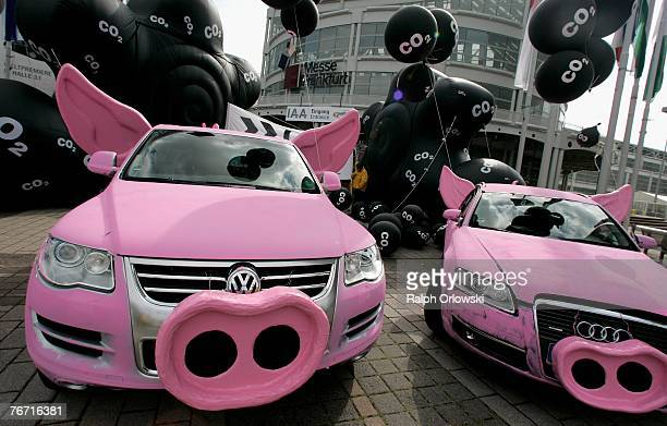 Greenpeace painted cars to make them look like pigs to demonstrate against CO2 emissions at an entrance to the IAA September 13 2007 in Frankfurt...