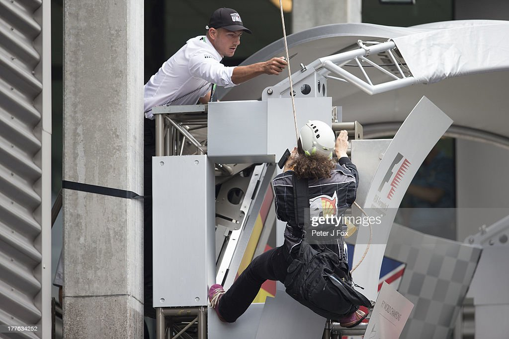 A Greenpeace Protester is threatened with her rope being cut durina demonstration at the Belgian Grand Prix at Circuit de Spa-Francorchamps on August 25, 2013 in Spa, Belgium.