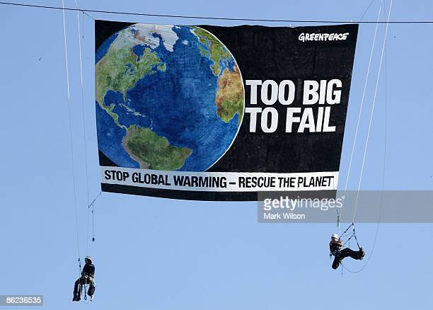 Greenpeace protesters hang with a banner from a construction crane on 23rd street near the State Department on April 27 2009 in Washington DC The...