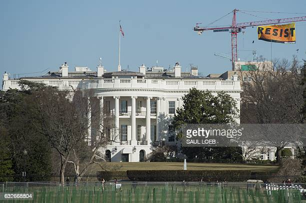 Greenpeace protesters unfold a banner reading 'Resist' from atop a construction crane behind the White House January 25 2017 in Washington DC The...