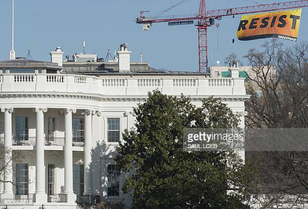 Greenpeace protesters unfold a banner reading 'Resist' from atop a construction crane January 25 2017 in Washington DC The banner flying high enough...