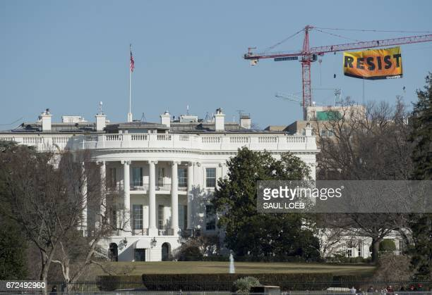 Greenpeace protesters unfold a banner reading 'Resist' from atop a construction crane behind the White House January 25 2017 in Washington DC While...