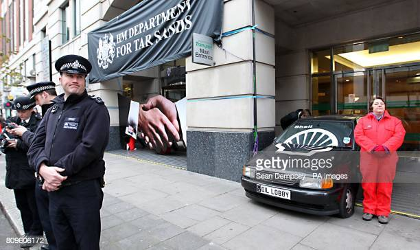 Greenpeace protesters use a car to block the main entrance to the Department for Transport in Horseferry Road London after they claimed documents...