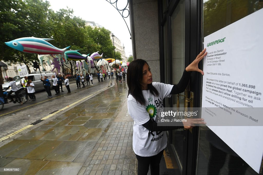 A Greenpeace protestor attaches a letter to the window of the Brazilian embassy during a parade of inflatable sea creatures protest on August 21, 2017 in London, England. The Greenpeace parade of inflatable sea creatures is making its way to the BP headquarters to protest at their plans to drill for oil near the recently discovered Amazon Reef, a 5000km2 coral reef in the Amazon Mouth Basin off the coast of Brazil.