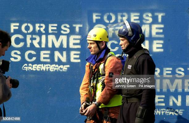 A Greenpeace protestor dressed as a workman is stopped and photographed by a police photographer before being led away by a riot policeman from...