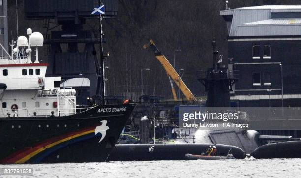 Greenpeace ship Arctic Sunrise sits next to the nuclear submarine HMS Vigilant that is docked at Faslane Naval Base Scotland