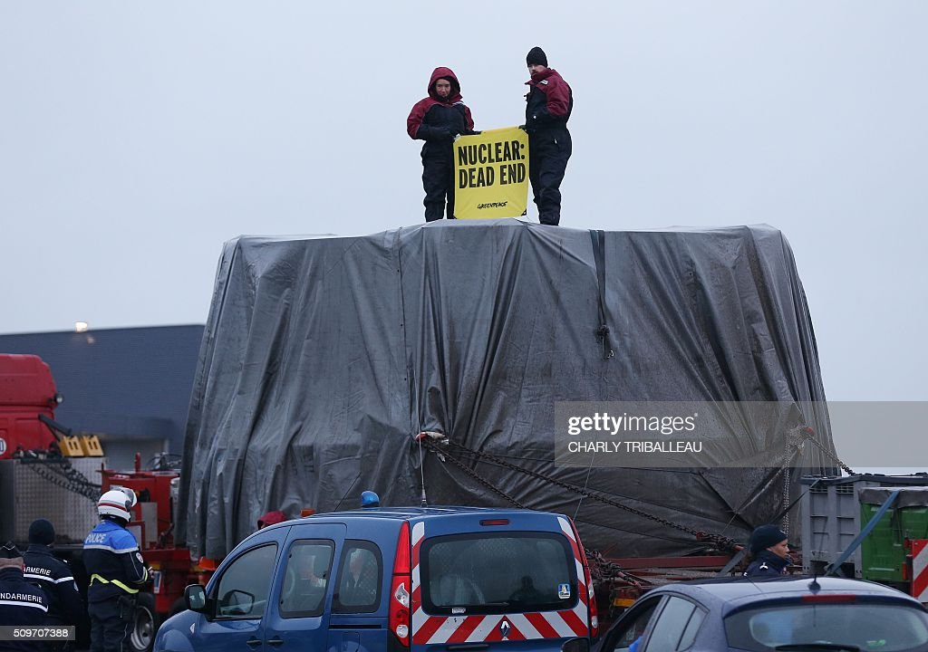 Greenpeace's activists hold a banner as they block a special convoy transporting a lid that is to be installed on the vessel of the nuclear reactor EPR, currently under construction at Flamanville, in Evrecy, northernwestern France, on February 12, 2016. The convoy transporting the lid of 110 tons that measures 5,5 meters in diameter left the Areva plant on Chalon-sur-Saône, eastern France, on the morning of February 8 and is expected to arrive at its destination on February 12. / AFP / CHARLY TRIBALLEAU