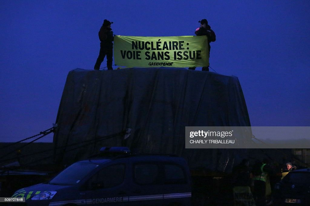 Greenpeace's activists hold a banner on the top of a trailer, reading 'Nuclear, dead end', as they block a special convoy transporting a lid that is to be installed on the vessel of the nuclear reactor EPR, currently under construction at Flamanville, in Evrecy, northernwestern France, on February 12, 2016. The convoy transporting the lid of 110 tons that measures 5,5 meters in diameter left the Areva plant on Chalon-sur-Saône, eastern France, on the morning of February 8 and is expected to arrive at its destination on February 12. / AFP / CHARLY TRIBALLEAU
