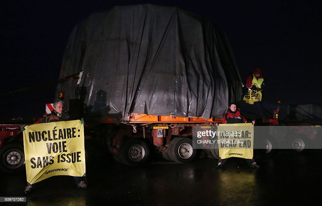 Greenpeace's activists hold banners as they block a special convoy transporting a lid that is to be installed on the vessel of the nuclear reactor EPR, currently under construction at Flamanville, in Evrecy, northernwestern France, on February 12, 2016. The convoy transporting the lid of 110 tons that measures 5,5 meters in diameter left the Areva plant on Chalon-sur-Saône, eastern France, on the morning of February 8 and is expected to arrive at its destination on February 12. / AFP / CHARLY TRIBALLEAU