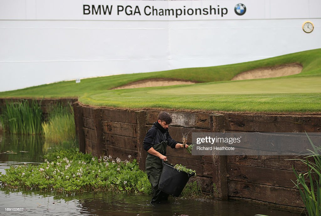 A greens keeper removes weeds from the pond around the 18th green during a practise day for the BMW PGA Championships at Wentworth on May 20, 2013 in Virginia Water, England.