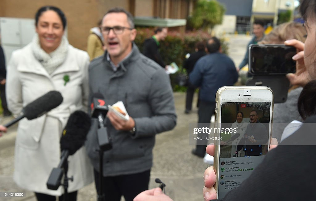 A Greens supporter films Leader of the Australian Greens Party Richard Di Natale (R) and Greens candidate for the seat of Batman Alex Bhathal (L) on her smart phone as they talk to to the media after casting their votes in the Australian Federal Election in Melbourne on July 2, 2016. Australia is voting in a general election which is expected to be a close race between the ruling Liberal-National coalition and the opposition Labor Party. / AFP / Paul Crock