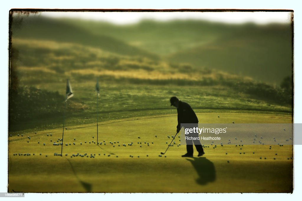 A greenskeeper collects the balls off the chipping green during the first round of the Open de Espana at Parador de El Saler on April 18 2013 in...