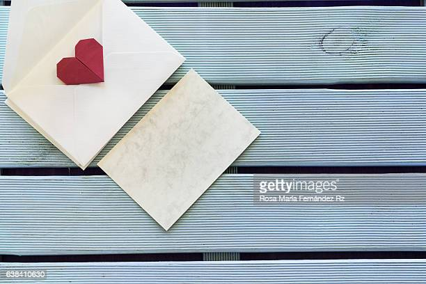 Greeting card and envelope with an origami heart, ready for love message. Subjects captured against soft window lighting. Copy space.