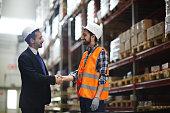 Happy foreman in helmet greeting one of warehouse workers