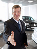 Greeting salesman in automobile showroom