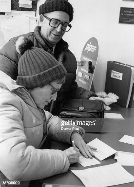 Greetings To Hostages Pat McBride of 12145 Albrook Drive Denver signs greeting card to one of American hostages in Iran while her husband Don looks...