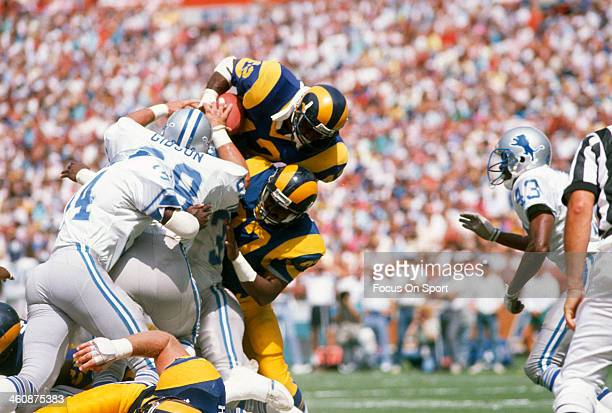 Greg Bell of the Los Angeles Rams dives over the top and gets hit by Dennis Gibson of the Detroit Lions during an NFL football game September 11 1988...