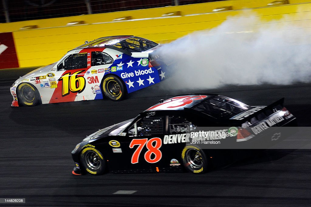 Greg Biffle blows the engine of the #16 3M/American Red Cross Ford as Regan Smith, driver of the #78 Furniture Row Racing Chevrolet, drives by during the NASCAR Sprint All-Star Race at Charlotte Motor Speedway on May 19, 2012 in Charlotte, North Carolina.