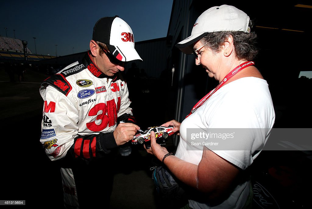 Greg Biffle, driver of the #16 3M ACE Bandage Ford, signs an autograph during practice for the NASCAR Sprint Cup Series Quaker State 400 presented by Advance Auto Parts at Kentucky Speedway on June 27, 2014 in Sparta, Kentucky.