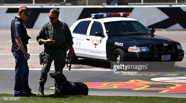 Greg Biffle driver of the 3M Ford Fusion participates in a narcotic detection exercise with Fort Worth Police officer Harald Cussnick and Kelev a...