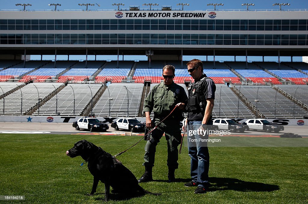 Greg Biffle, driver of the #16 3M Ford Fusion, participates in a narcotic detection exercise with Fort Worth Police officer Harald Cussnick and Kelev, a Fort Worth Police Department K-9, during an exhibition at Texas Motor Speedway on March 20, 2013 in Fort Worth, Texas.