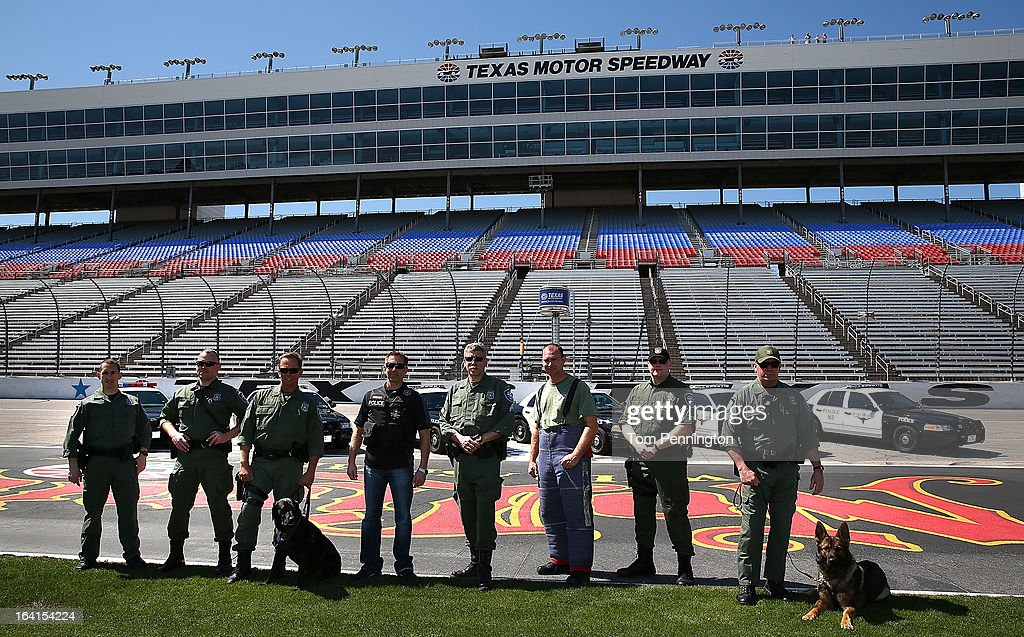 Greg Biffle (C), driver of the #16 3M Ford Fusion, poses for a group photo with officers of the Fort Worth Police Department K-9 Unit during an exhibition at Texas Motor Speedway on March 20, 2013 in Fort Worth, Texas.