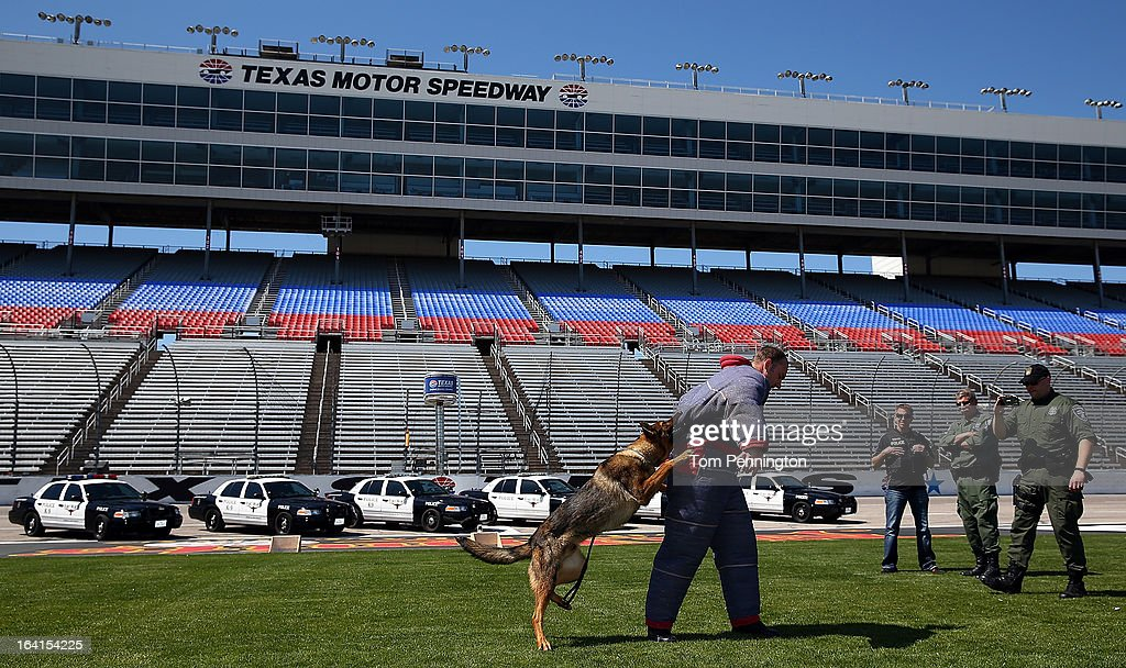 Greg Biffle (3rd from R), driver of the #16 3M Ford Fusion, watches a Fort Worth Police Department K-9 exercise during an exhibition at Texas Motor Speedway on March 20, 2013 in Fort Worth, Texas.